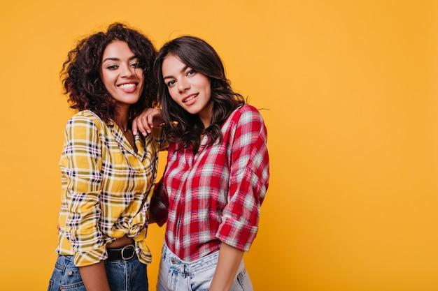 Ritratto del primo piano di giovani donne in camicie a scacchi. le ragazze dagli occhi marroni sorridono carine.