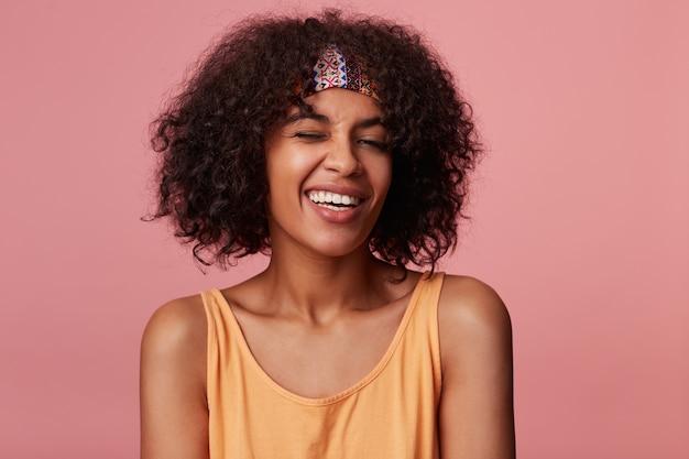 Close-up di positivo attraente giovane donna dalla pelle scura con capelli castani ricci che indossa acconciatura casual, guardando allegramente con un sorriso affascinante e dando occhiolino, isolato