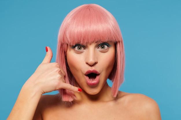 Close-up di positivo dagli occhi verdi giovane bella signora con taglio di capelli rosa alla moda che arrotonda la bocca mentre guarda allegramente camara, piegando la mano alzata nel microtelefono, isolato su sfondo blu