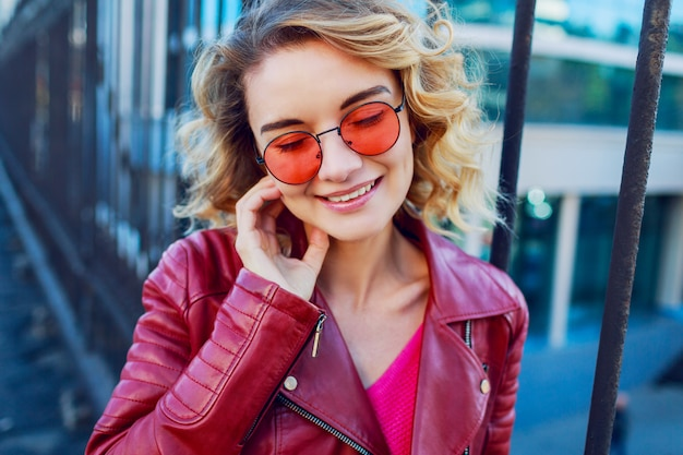 Close up positive portrait of cheerful happy woman in pink pullover