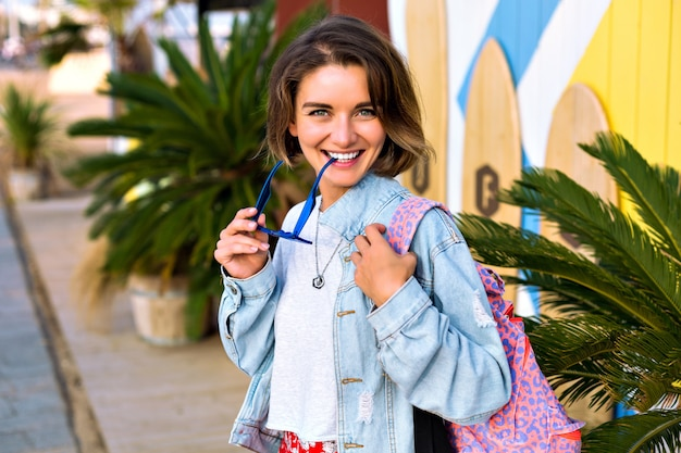Chiuda sul ritratto positivo della donna alla moda hipster in posa davanti al surf spot, abbigliamento alla moda giovanile, occhiali da sole blu, giacca di jeans e zaino, palme intorno.