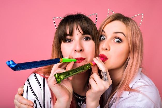 Chiuda sul ritratto positivo di due donne hipster felici divertendosi, utilizzando accessori per feste, chiuda sul ritratto pazzo, tempo di amicizia