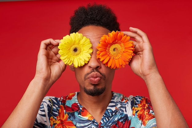 Close up positive young african american guy, wears in hawaiian shirt, looks at the camera trough flowers with happy expression, send kiss at the camera, stands over red background.