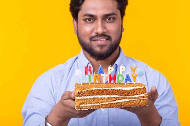 Close-up of positive young man holding a happy birthday cake and two burning bengal lights posing on