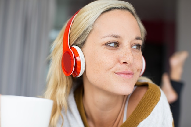 Close-up of positive young woman in headphones