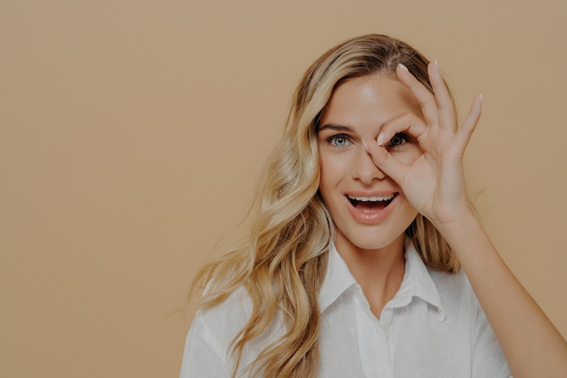 Close up of positive young woman with long wavy fair hair looking at camera through fingers folded into ok gesture, opens mouth with excitement while posing isolated over beige background
