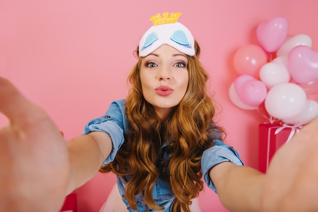 Postrait del primo piano della ragazza adorabile di compleanno che posa al mattino con palloncini e regali dietro di lei. affascinante giovane donna riccia in elegante maschera per dormire facendo selfie prima della festa, in attesa di celebrazione