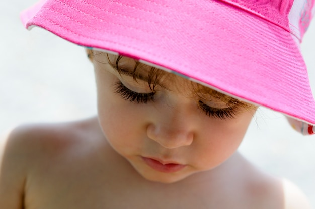Close-up potrait of adorable little girl outdoors wearing sun hat.
