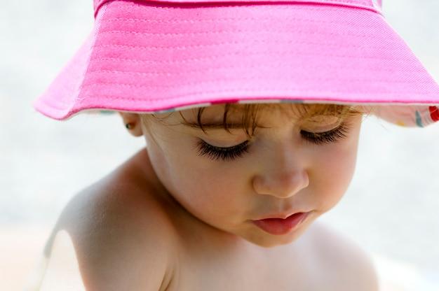 야외에서 태양 모자를 쓰고 사랑스러운 작은 소녀의 근접 potrait.