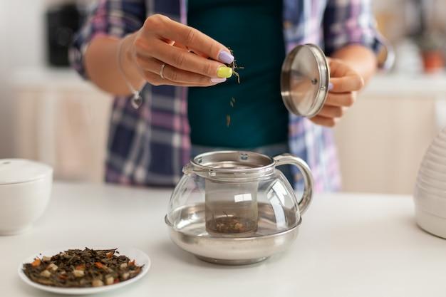 Primo piano di versare erbe aromatiche in teiera per preparare il tè al mattino per colazione