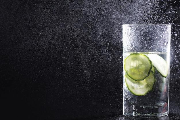 リビングルームのテーブルにボトルから精製された新鮮な飲料水を注ぐクローズアップ