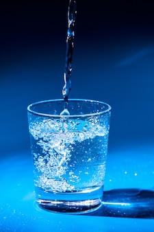 Крупным планом лить очищенную питьевую воду из бутылки на столе