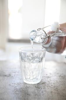 Крупным планом наливание воды в стакан
