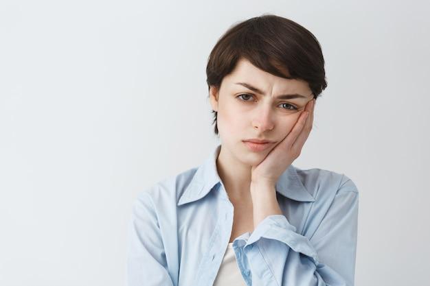 Primo piano della ragazza triste e delusa imbronciata che sembra riluttante, accigliata sconvolta