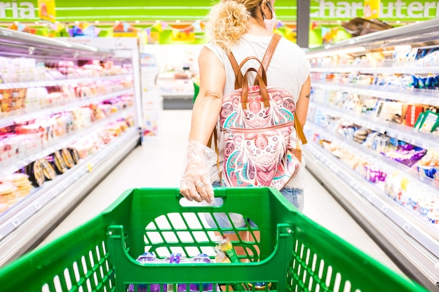 Close up and pov of a man pushing a shopping cart with a woman buying food and products in the supermarket