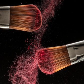 Close up powder splash and brush for makeup artist or beauty blogger in black background