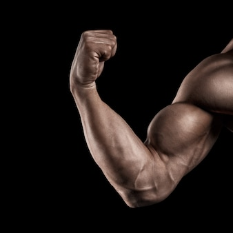 Close-up of a power fitness man's hand. strong and handsome young man with muscles and biceps. studio shooting on black background.