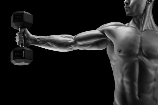 Close-up of a power fitness man's hand with dumbbell. strong bodybuilder with six pack, perfect abs, shoulders, biceps, triceps and chest, deltoid muscle. black and white photo.