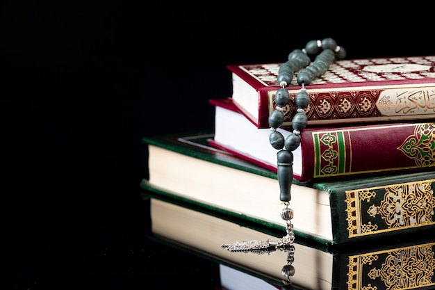 Close up prayer beads on pile of books