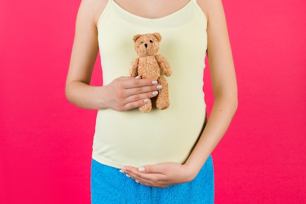 Close up of pregnant woman in colorful home clothing holding a teddy bear against her belly