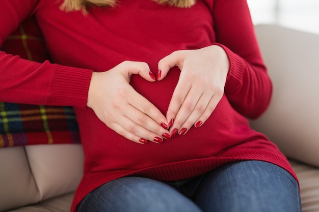Close up of a pregnant woman doing heart sign on her belly