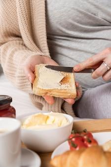ブランチを家で食べるクローズアップ妊娠中の女性