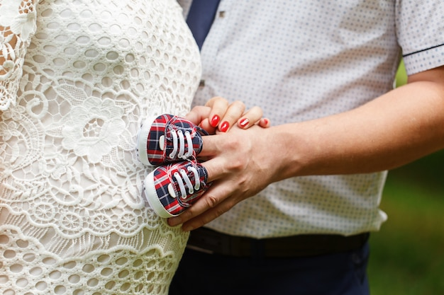 Close-up of a pregnant woman and her husband holding baby shoes