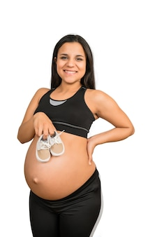 Close-up of pregnant woman holding baby shoes on belly