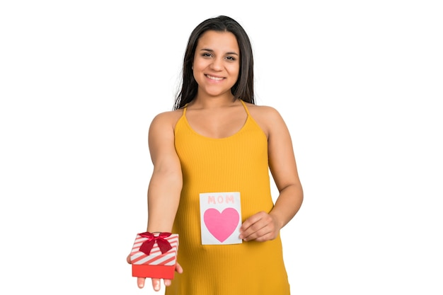 Close-up of pregnant woman holding greeting card and gift box against white wall. pregnancy, new mom and motherhood concept.