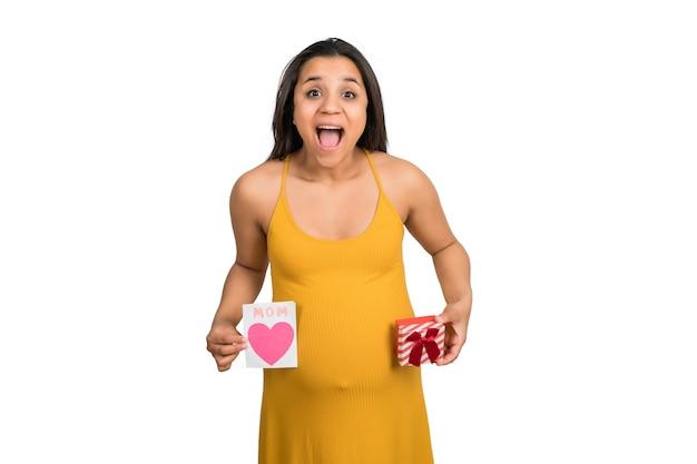 Primo piano della donna incinta che tiene biglietto di auguri e confezione regalo