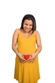 Close-up of pregnant woman holding heart sign on belly against white wall. pregnancy, motherhood concept.