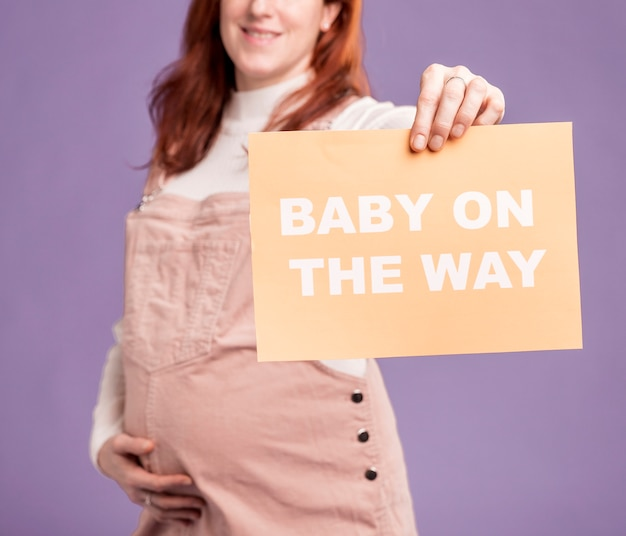 Close-up pregnant woman holding paper with baby on the way message