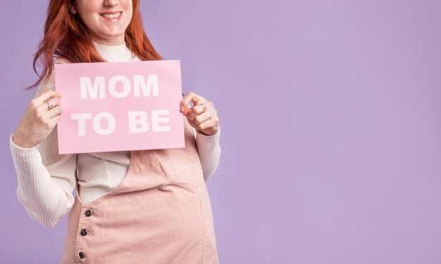Close-up pregnant woman  holding paper with mom to be message