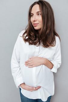 Крупным планом беременная женщина, глядя в сторону изолированный серый фон