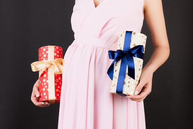 Close up of pregnant woman in pink dress holding two gift boxes at black background. is it a boy or a girl? expecting twins. childbirth preparation. copy space.