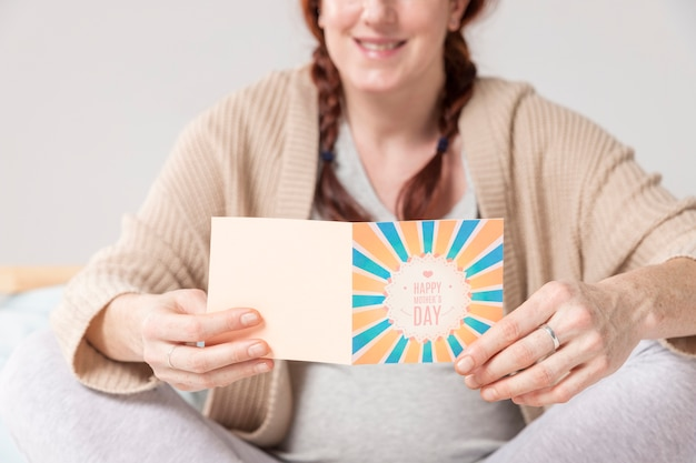 Close-up pregnant woman reading greeting card