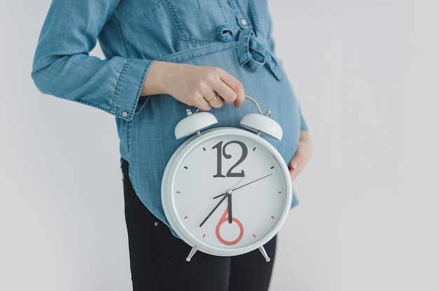 Close-up of pregnant woman showing clock