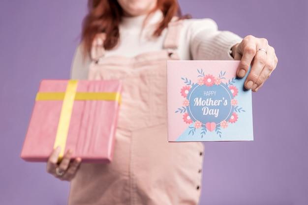 Беременная женщина конца-вверх показывая подарок и поздравительную открытку