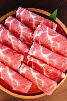 Close up premium rare slices kurobuta (black pig) pork with low-marbled texture.