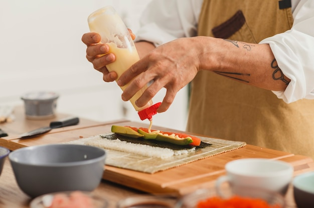 쌀과 연어 생선 온라인 음식 배달로 초밥을 만드는 롤 요리사 준비를 닫습니다.