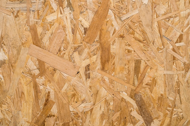Close up pressed wooden panel background, seamless texture of oriented strand board - osb wood.