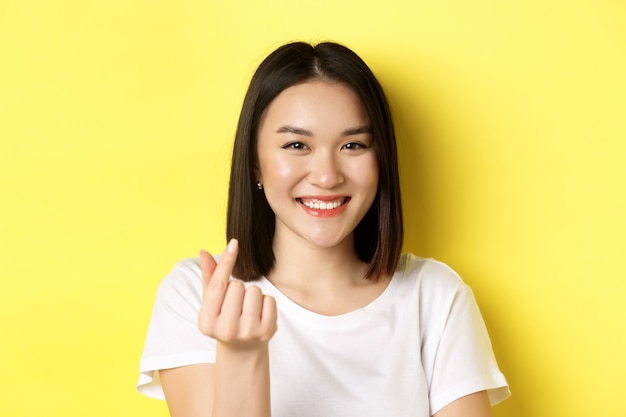 Close up of pretty asian girl in white t-shirt, smiling and showing finger heart, standing over yellow.