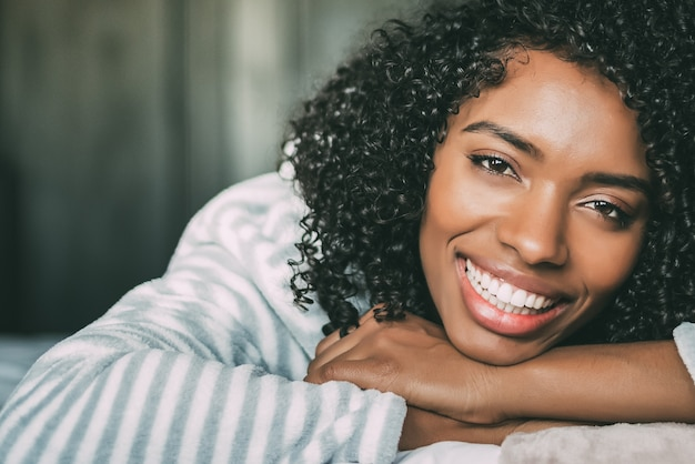 Close up of a pretty black woman with curly hair smiling and lying on bed looking at the camera