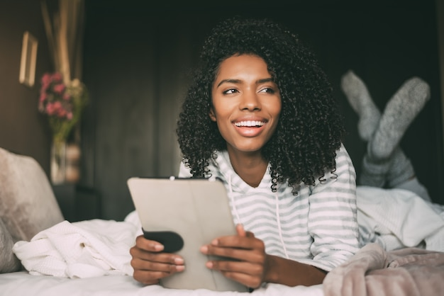 Close up of a pretty black woman with curly hair smiling and using phone on bed looking away