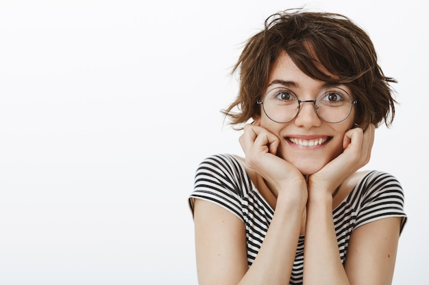 Primo piano della donna graziosa ed eccitata che sorride, cercando con tentazione che qualcosa accada, ammirazione dello sguardo