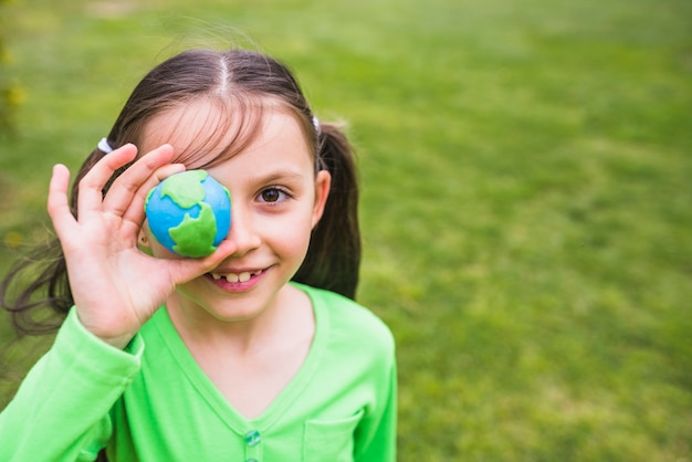 Close-up of a pretty girl holding clay globe in hand