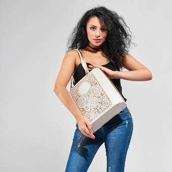 Close-up of a pretty girl with black curly hair,wearing black top and blue jeans. she carries white fashionable bag with stamping and handles.