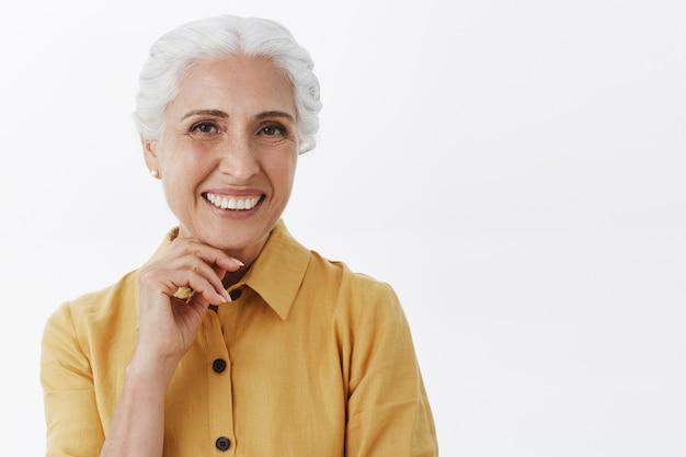 Primo piano della signora anziana sorridente abbastanza felice che sembra soddisfatta