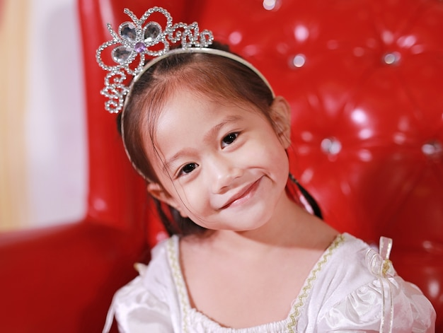 Close-up pretty little girl in beautiful luxurious dress with crown sitting