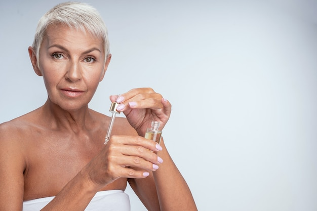 Close up of a pretty mature lady putting serum on her hand